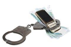 Handcuffs met mobiel geïsoleerde telefoon en geld Stock Foto's
