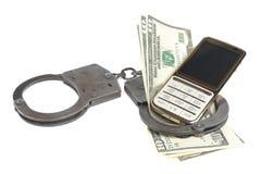 Handcuffs met mobiel geïsoleerde telefoon en geld Royalty-vrije Stock Fotografie