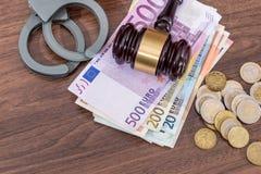 Handcuffs met wetshamer en euro rekeningen, muntstuk op bureau Royalty-vrije Stock Foto