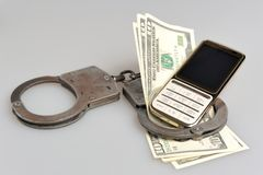 Handcuffs with mobile phone and money on gray. Background Royalty Free Stock Image