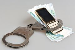 Handcuffs with mobile phone and money isolated. Handcuffs with mobile phone and money on white background Royalty Free Stock Photography