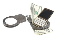 Handcuffs with mobile phone and money isolated Royalty Free Stock Photography
