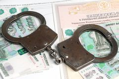 Handcuffs and money against the background of the certificate of. Handcuffs, money against the background of the certificate of registration of property rights Stock Photos