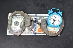 Handcuffs, money and alarm clock on dark background, bail concept. Handcuffs, money and blue alarm clock on dark background, bail concept stock image