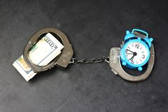 Handcuffs, money and alarm clock on dark background, bail concept. Handcuffs, money and blue alarm clock on dark background, bail concept royalty free stock images
