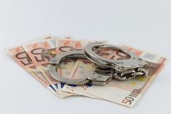 Handcuffs on money bills Royalty Free Stock Photo