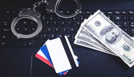 Handcuffs, money, credit cards on computer keyboard. Concept of Cyber crime and Online fraud stock photos