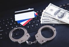 Handcuffs, money, credit cards on computer keyboard. Concept of Cyber crime and Online fraud royalty free stock image