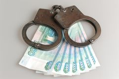 Handcuffs and money on gray. Background Royalty Free Stock Photos