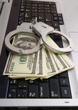 Handcuffs and money on laptop Royalty Free Stock Photography