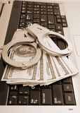 Handcuffs and money on laptop Royalty Free Stock Images
