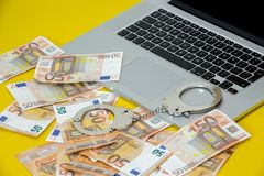 Handcuffs with money on the laptop keyboard. royalty free stock image
