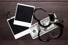 Handcuffs money and old photos detective concept Stock Image