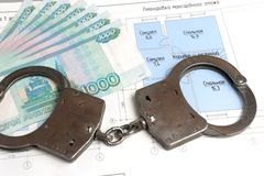 Handcuffs, money with the plan of the house. On a white background Royalty Free Stock Image