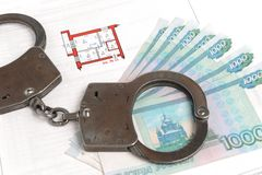 Handcuffs, money and technical passport with the plan. Of the apartments Stock Photography