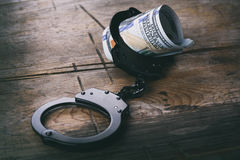 Handcuffs with money on wooden background Royalty Free Stock Photos