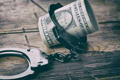 Handcuffs and money on wooden table Royalty Free Stock Photo