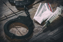 Handcuffs and narcotic. On a wooden background Royalty Free Stock Images