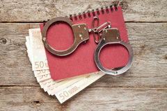 Handcuffs on notebook with euro banknotes Stock Photography