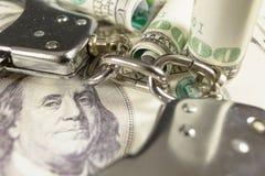 Handcuffs op een dollar factureert royalty-vrije stock afbeeldingen