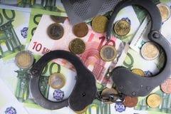 Handcuffs op een stapel van euro bankbiljetten r stock fotografie