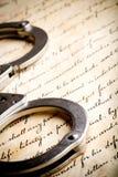 Handcuffs op grondwet Stock Afbeelding