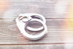 Handcuffs, a pair of wedding rings. On a wooden table. marriage, marriage. love. a family Stock Photo
