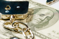 Handcuffs on a pile of dollar bills Royalty Free Stock Photos