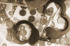 Handcuffs on a pile of euro banknotes. The symbolic meaning of economic crimes. Copy paste Stock Photography