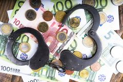 Handcuffs on a pile of euro banknotes. The symbolic meaning of economic crimes. Copy paste Royalty Free Stock Image