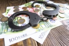 Handcuffs on a pile of euro banknotes. The symbolic meaning of economic crimes. Copy paste Stock Image