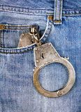 Handcuffs in the Pocket. Of the Jeans closeup royalty free stock photo