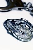 Handcuffs and police badge. Close-up detail of a police metal badge and handcuffs Stock Image