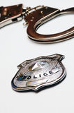 Handcuffs and police badge. Close-up detail of a police metal badge and handcuffs Stock Images