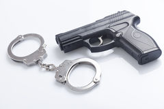 Handcuffs and police gun Royalty Free Stock Photography