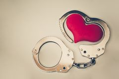 Handcuffs with a red love heart. With copy space to add text Stock Image