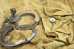 Handcuffs, Security Concept On  Camouflage Backpack Background Royalty Free Stock Image