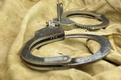 Handcuffs, Security Concept On  Camouflage Backpack Background Stock Photo