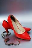 Handcuffs and high heels. Metal handcuffs and high heels stock photos