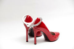 Handcuffs and sexy red high heels. bdsm. Handcuffs and sexy red high heels on white background, bdsm Stock Photos