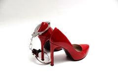 Handcuffs and sexy red high heels. bdsm. Handcuffs and sexy red high heels on white background, bdsm Royalty Free Stock Photos