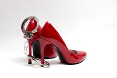 Handcuffs and sexy red high heels. bdsm. Handcuffs and sexy red high heels on white background. bdsm Royalty Free Stock Image