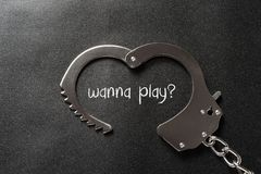 Handcuffs shaped like a heart on black and writtting with wanna play. ? Royalty Free Stock Photos