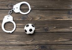 Handcuffs, soccer ball. illegal actions. Handcuffs, soccer ball on a wooden background. Football fans. riots in the stadium. illegal actions Stock Image