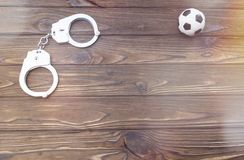 Handcuffs, soccer ball on a wooden background. Unlawful actions of football fans Stock Photos