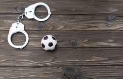 Handcuffs, soccer ball on a wooden background. Unlawful actions of football fans Stock Photo