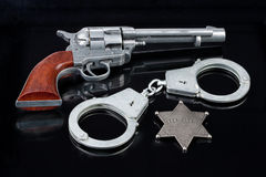 Handcuffs, Star And Revolver Stock Photography
