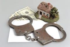 Handcuffs, stuk speelgoed huis en witte envelop met geld op grijs Royalty-vrije Stock Fotografie