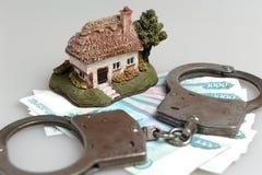 Handcuffs, stuk speelgoed huis en witte envelop met geld op grijs Stock Foto's