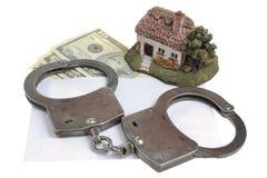 Handcuffs, stuk speelgoed huis en witte envelop met geld op witte rug Royalty-vrije Stock Afbeeldingen
